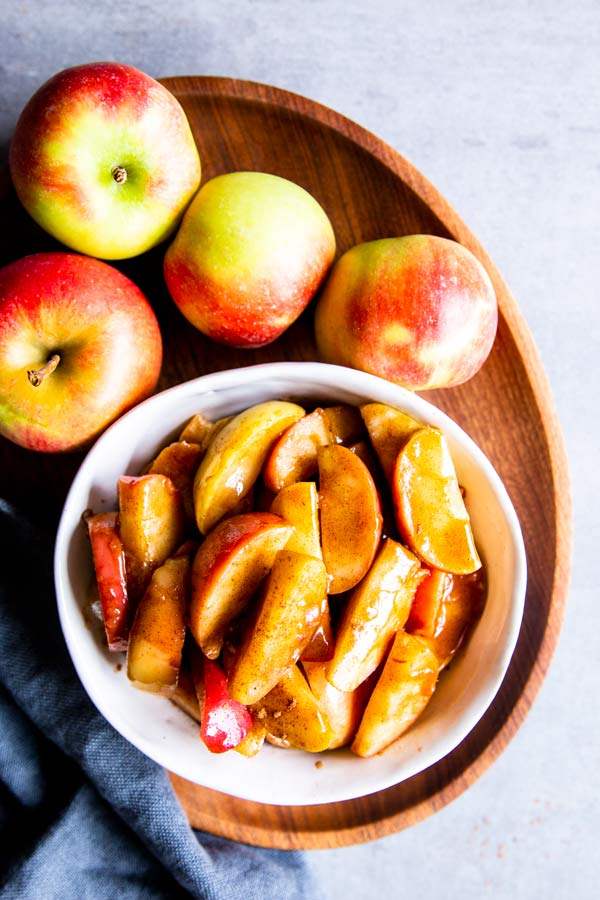 cinnamon apples in a bowl on a wooden tray with fresh apples around