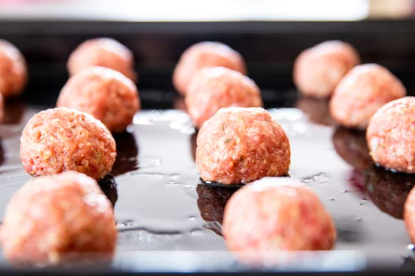 homemade meatballs raw on a baking sheet