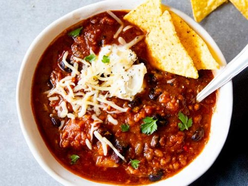 instant pot pumpkin chili in a white bowl with toppings and corn chips