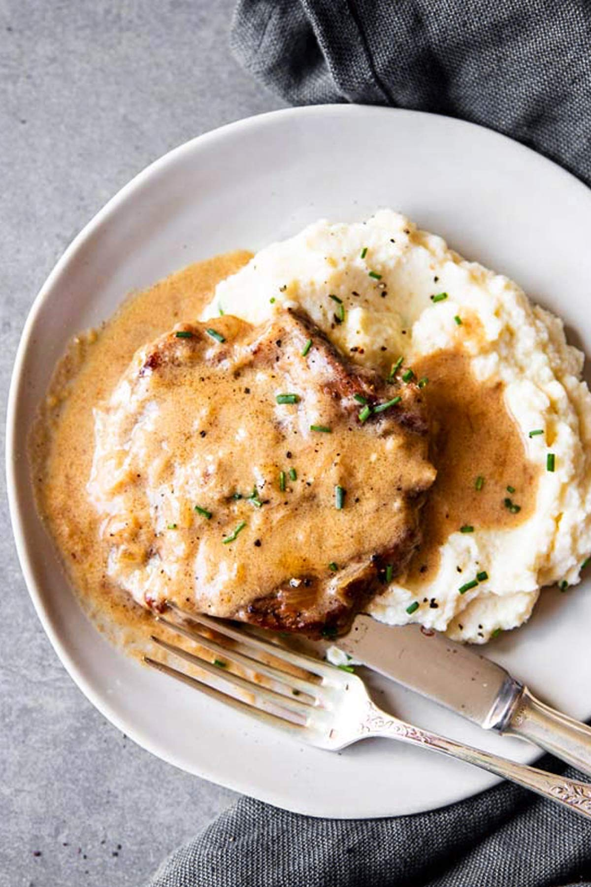 instant pot sour cream pork chop on a plate with mashed cauliflower