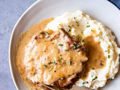 instant pot sour cream pork chops on a plate with mashed cauliflower