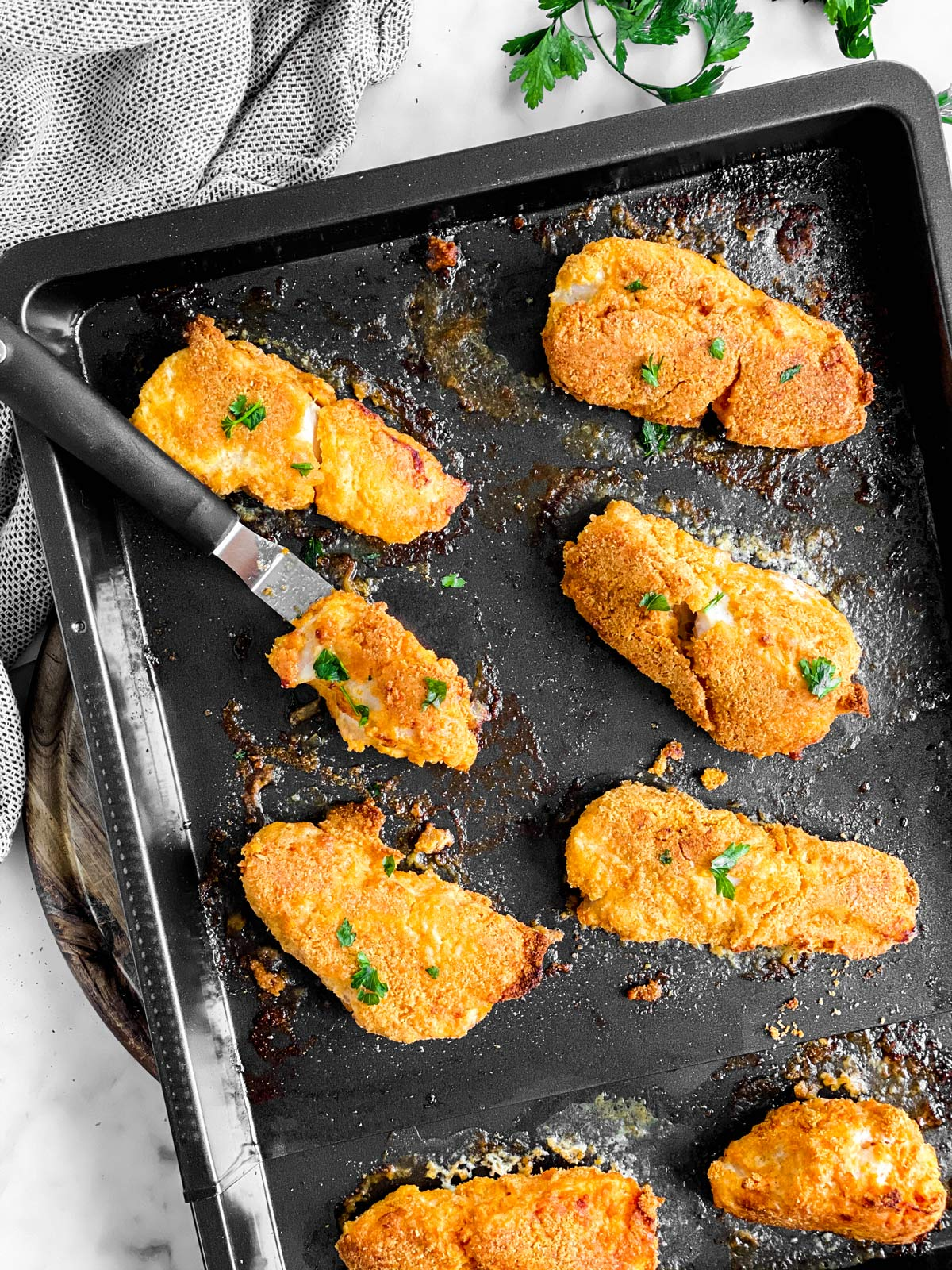 black pan with pieces of low carb oven fried fish
