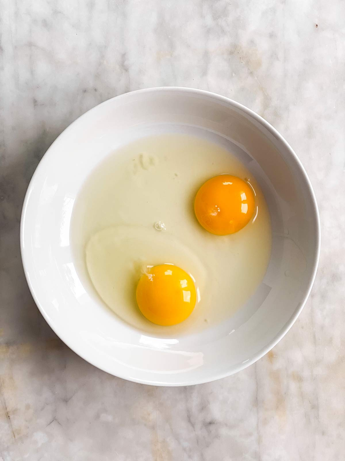 white bowl with two cracked eggs inside