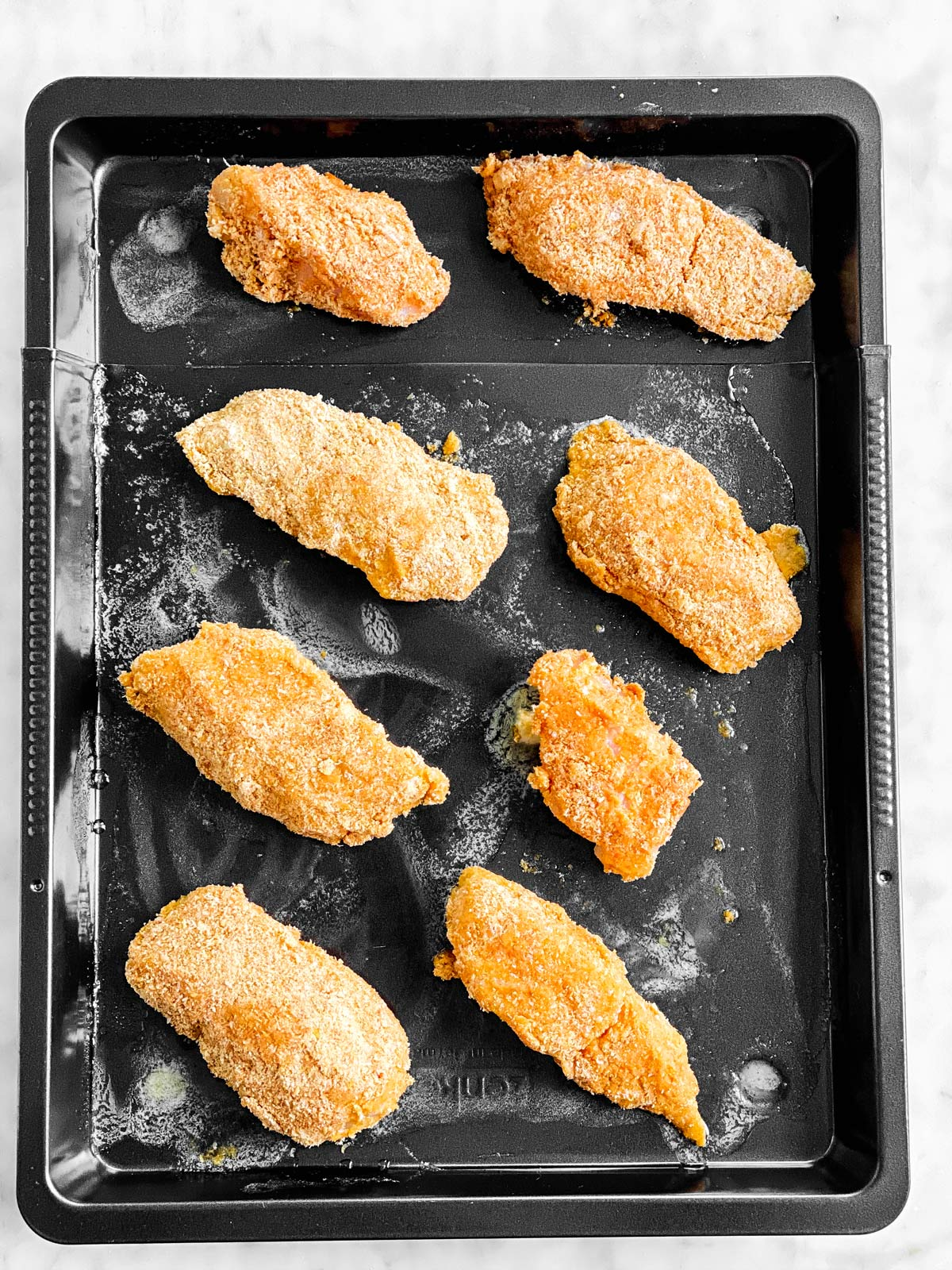 black pan with unbaked breaded fish