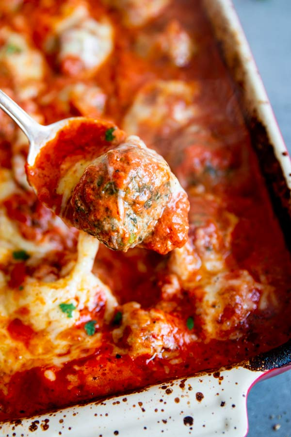scooping meatballs out of a meatball casserole with a large spoon