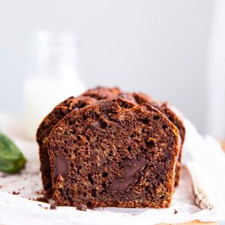 sliced chocolate zucchini bread on a wooden board with a bottle of milk