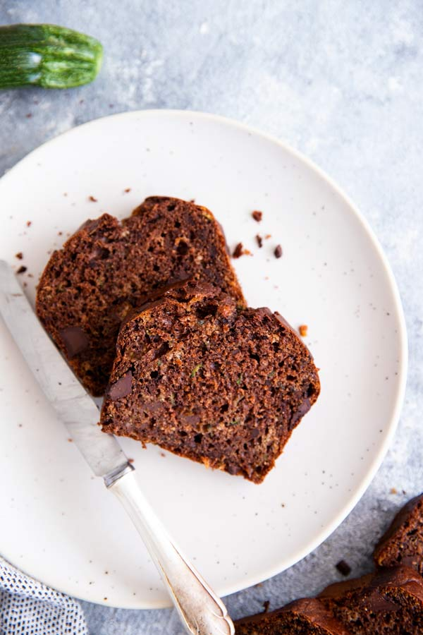 two slices of healthy double chocolate zucchini bread on a white plate