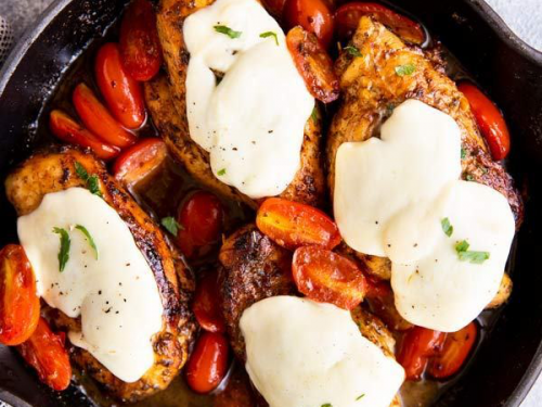 black cast iron skillet with balsamic glazed caprese chicken