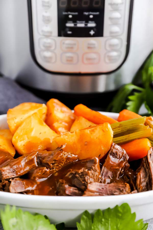 plate with instant pot pot roast in front of a pressure cooker