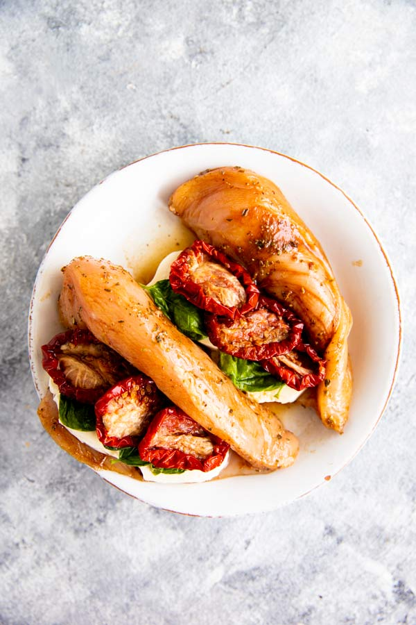 chicken breast cut open and filled with caprese ingredients