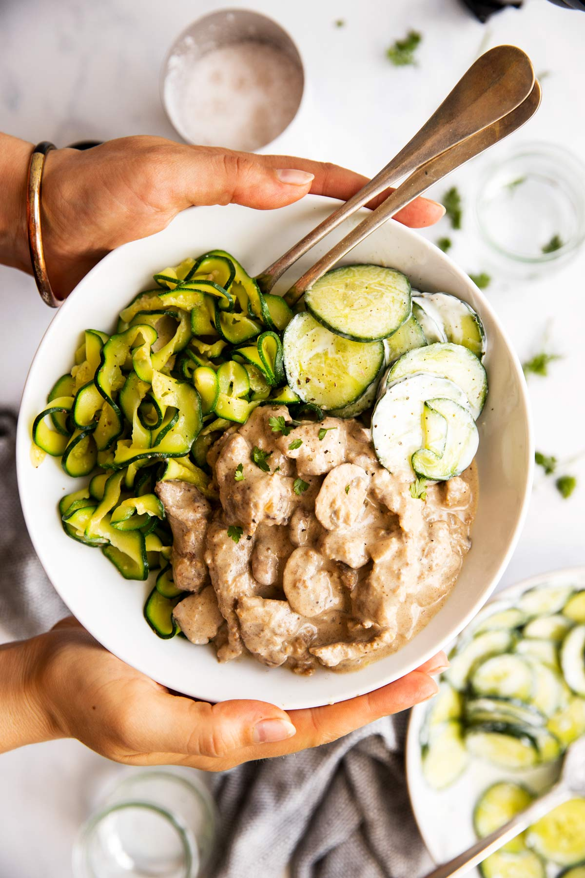 female hands holding a plate filled with stroganoff and low carb side dishes