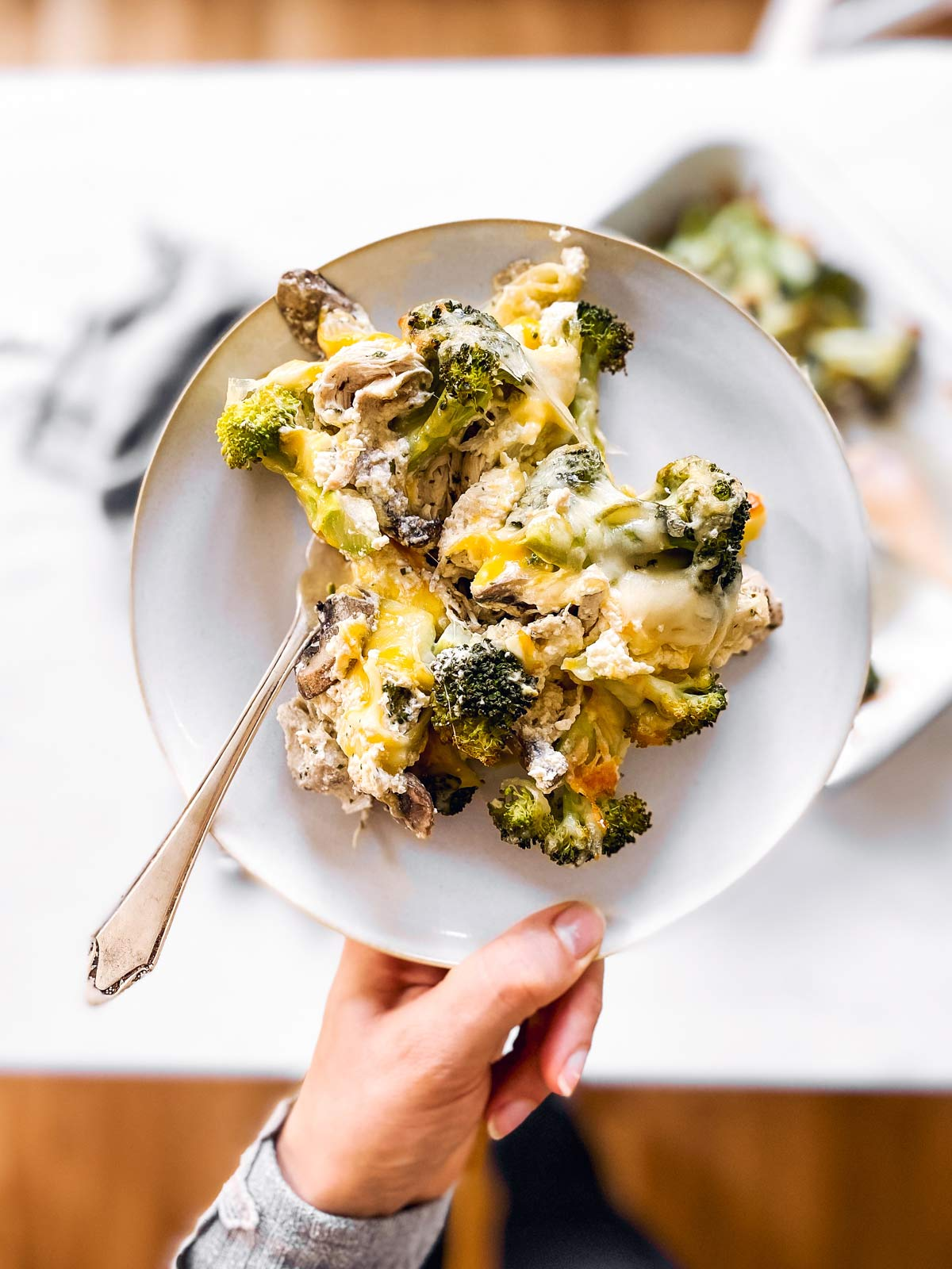 female hand holding a plate with chicken broccoli casserole