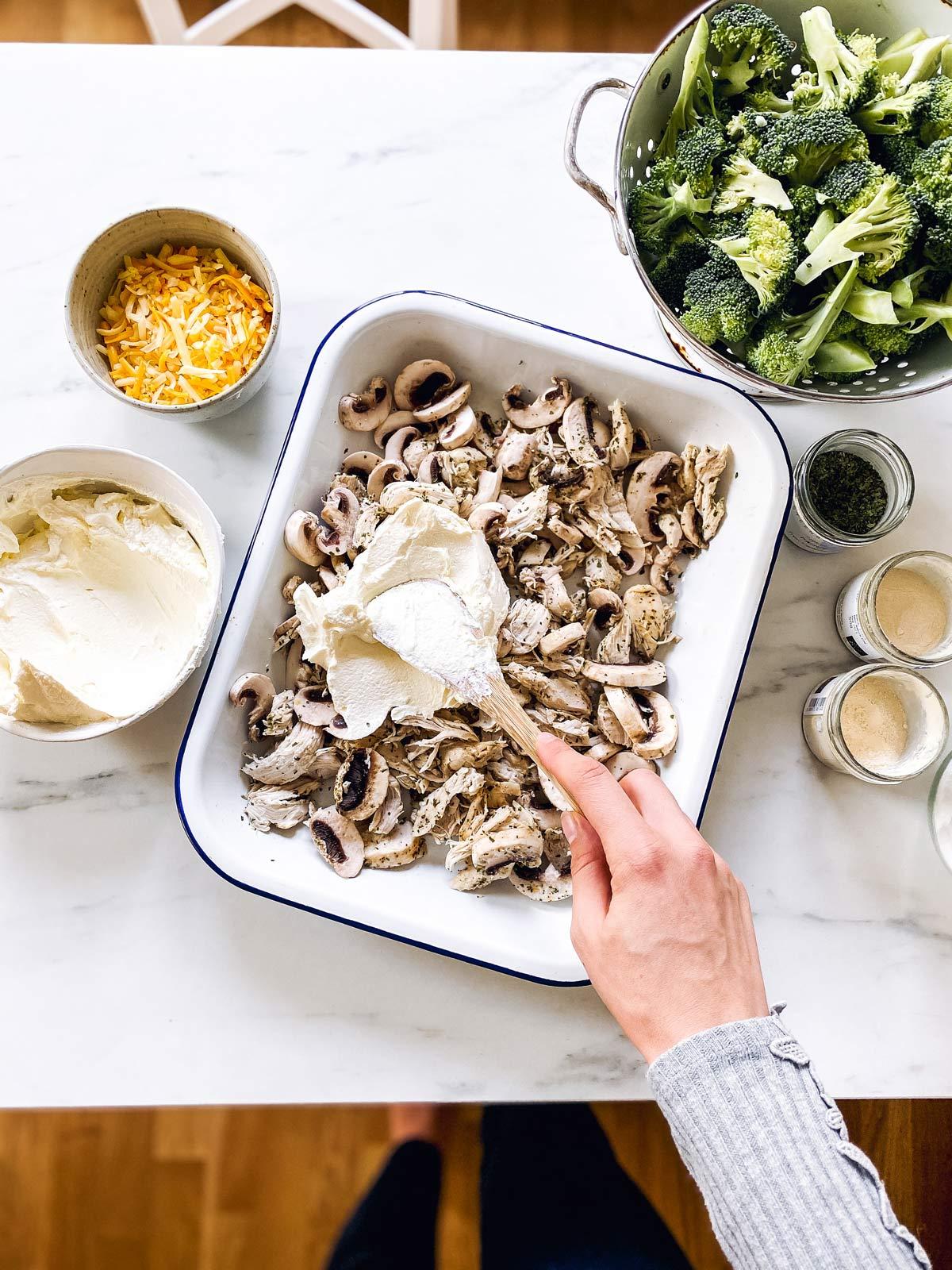 female hand spreading cream cheese over chicken in casserole dish