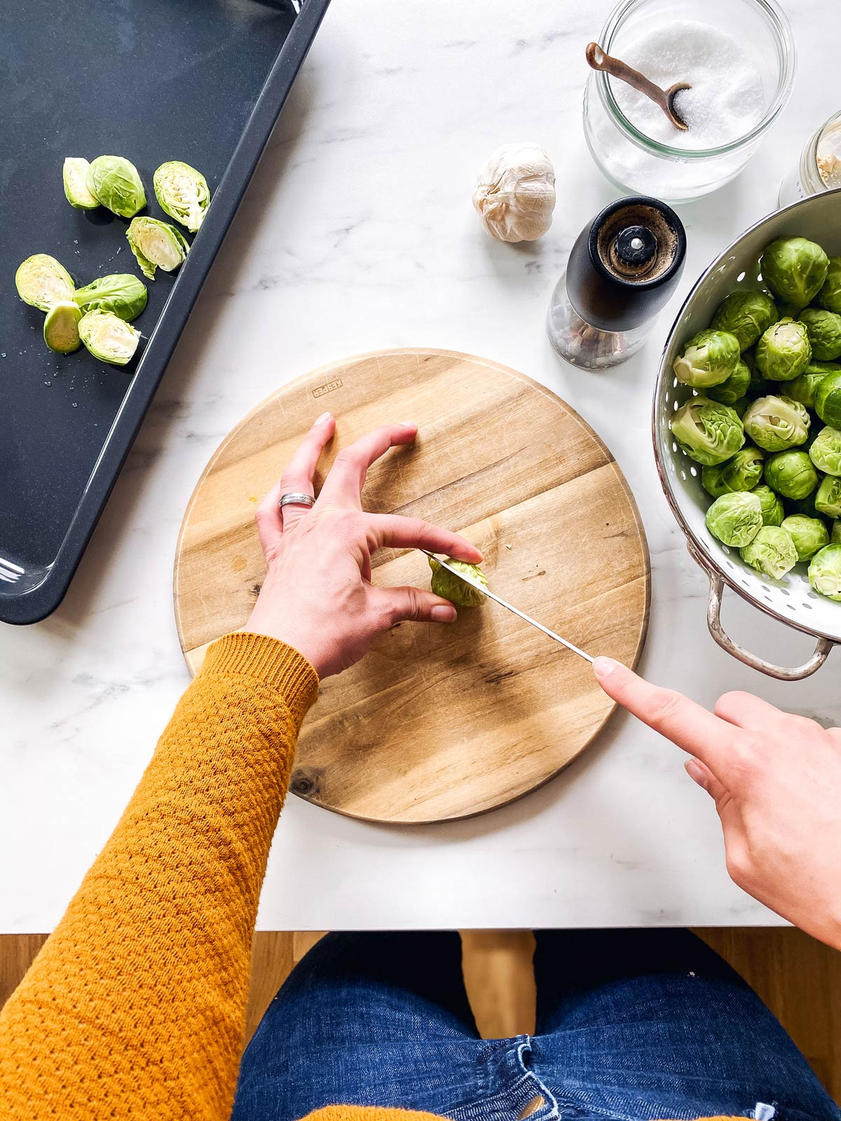 female hands slicing a Brussels sprout in half