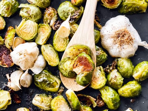 roasted Brussels sprouts on a sheet pan with a wooden spoon