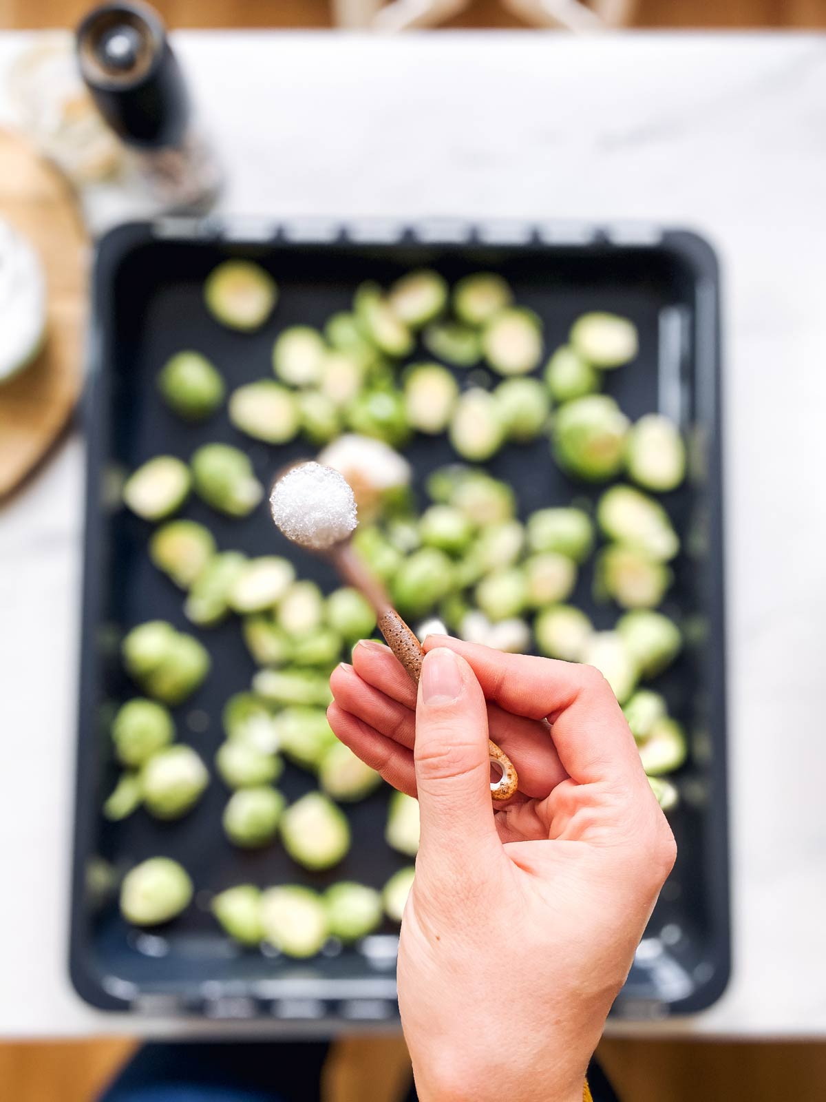 spoonful of salt help over a sheet pan with Brussels sprouts