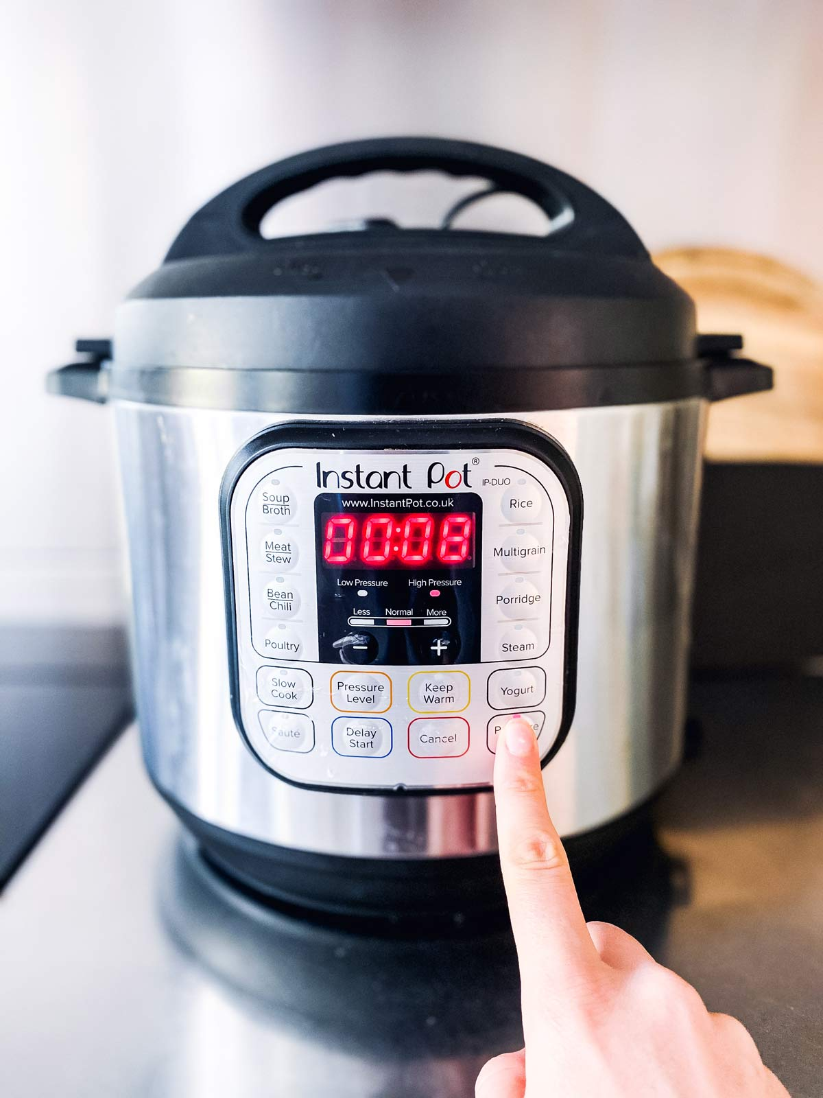 female hand setting the instant pot timer