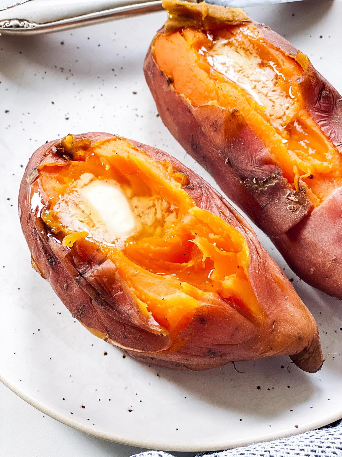 close up photo of sliced open sweet potatoes with butter on top