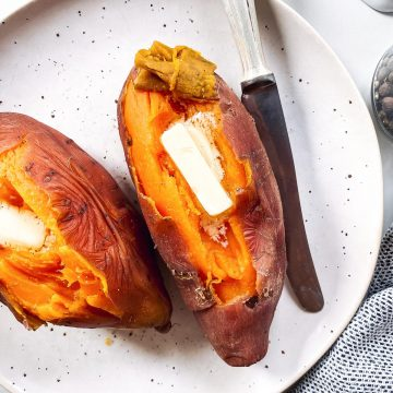 overhead view of two steamed sweet potatoes on a white plate