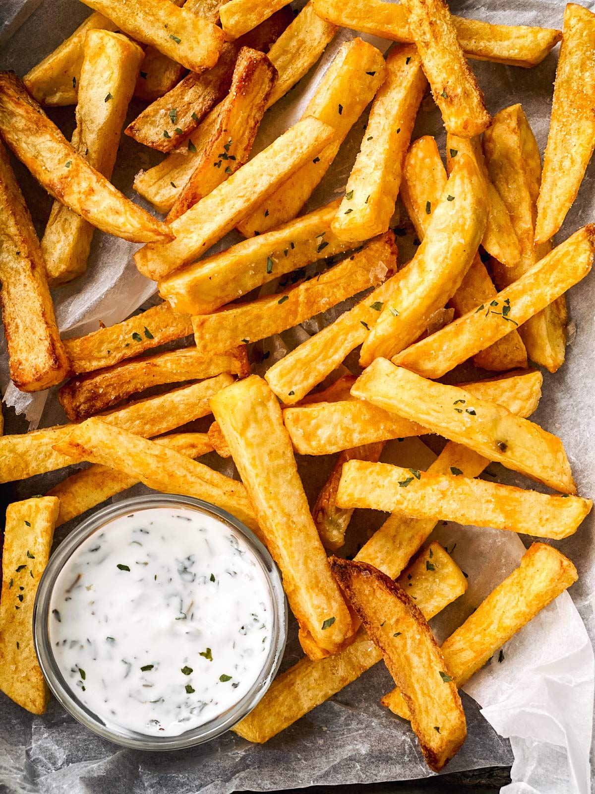 overhead view of air fryer French fries on line pan with ranch dip