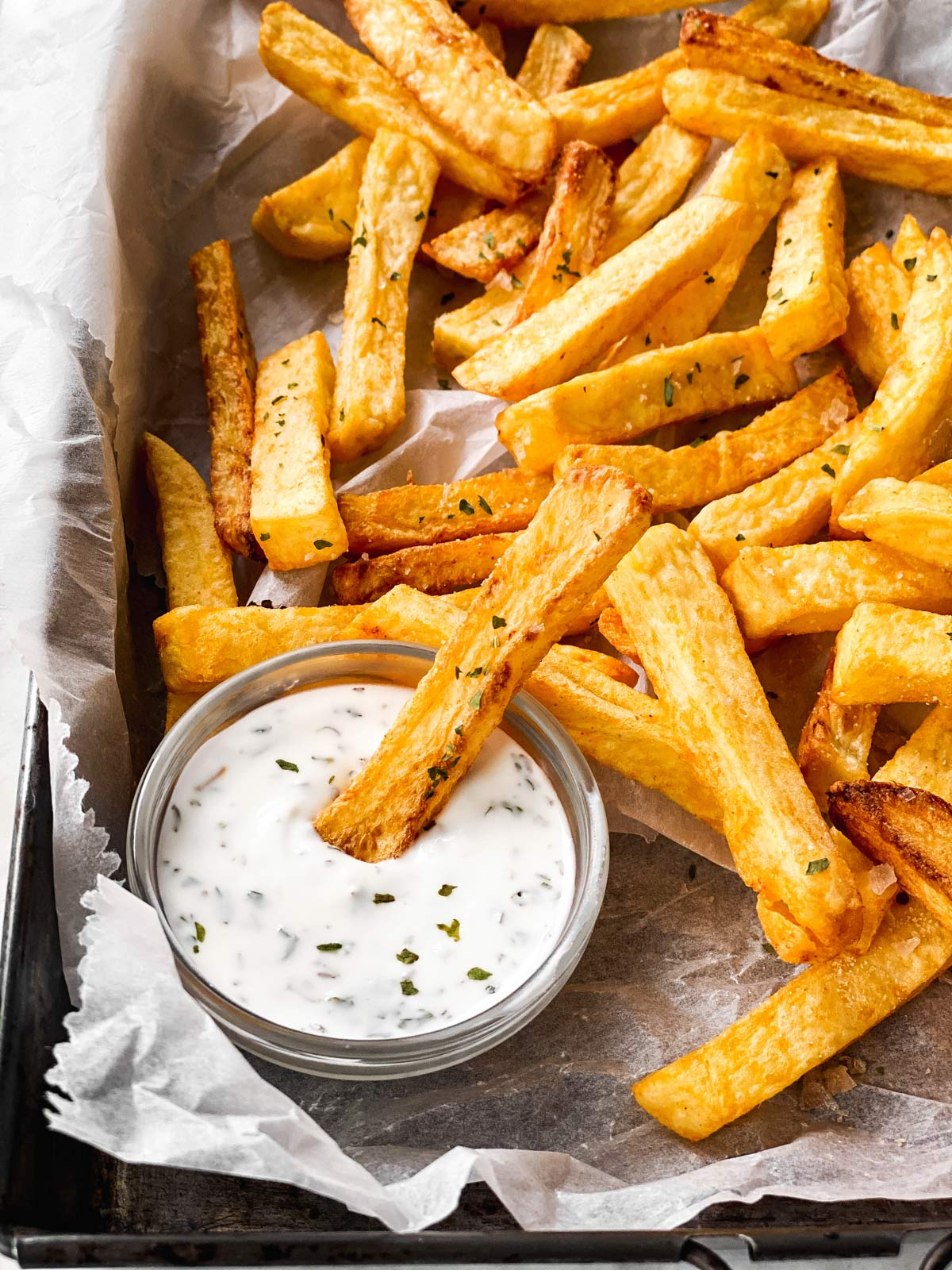 French fry dipped in ranch on tray with other French fries