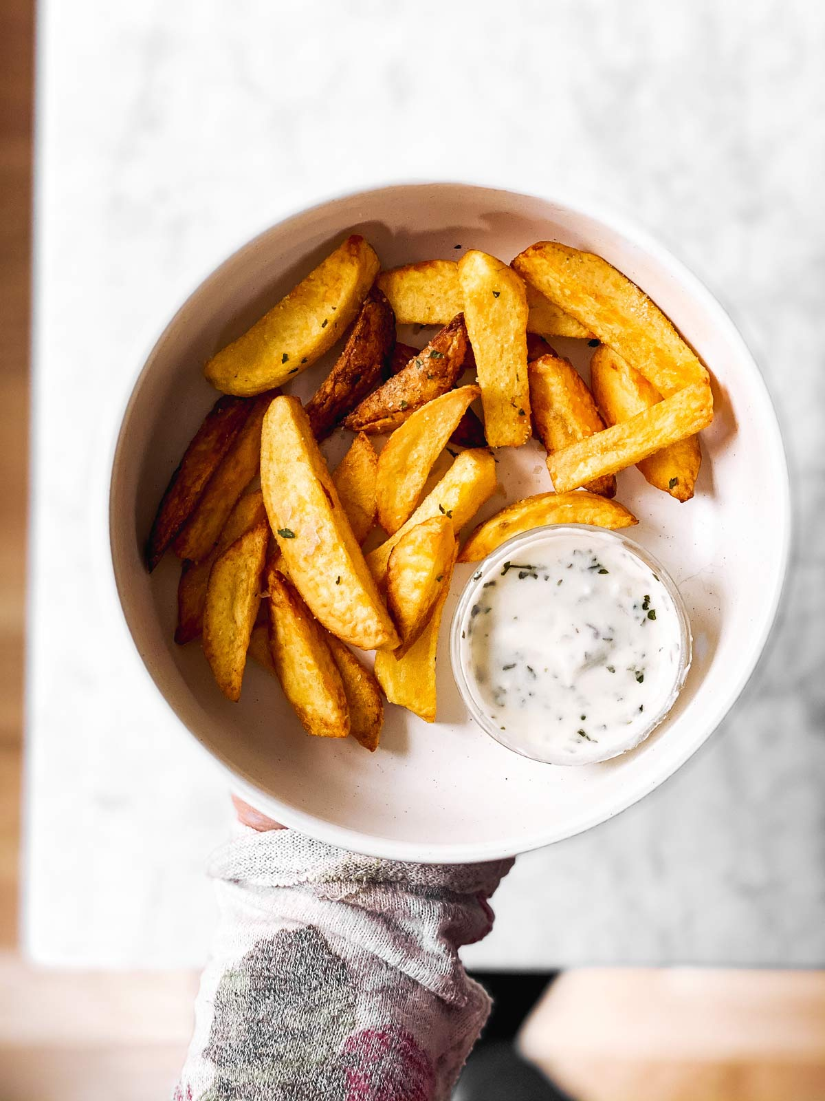 female hand holding bowl with air fryer French fries and ranch dip