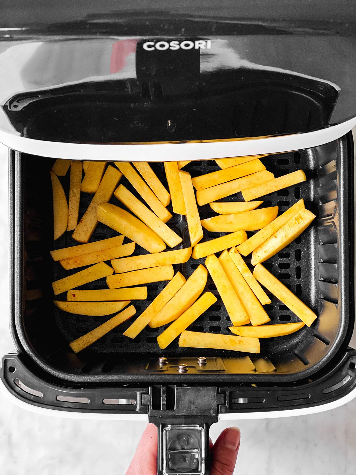 uncooked French fries in air fryer basket