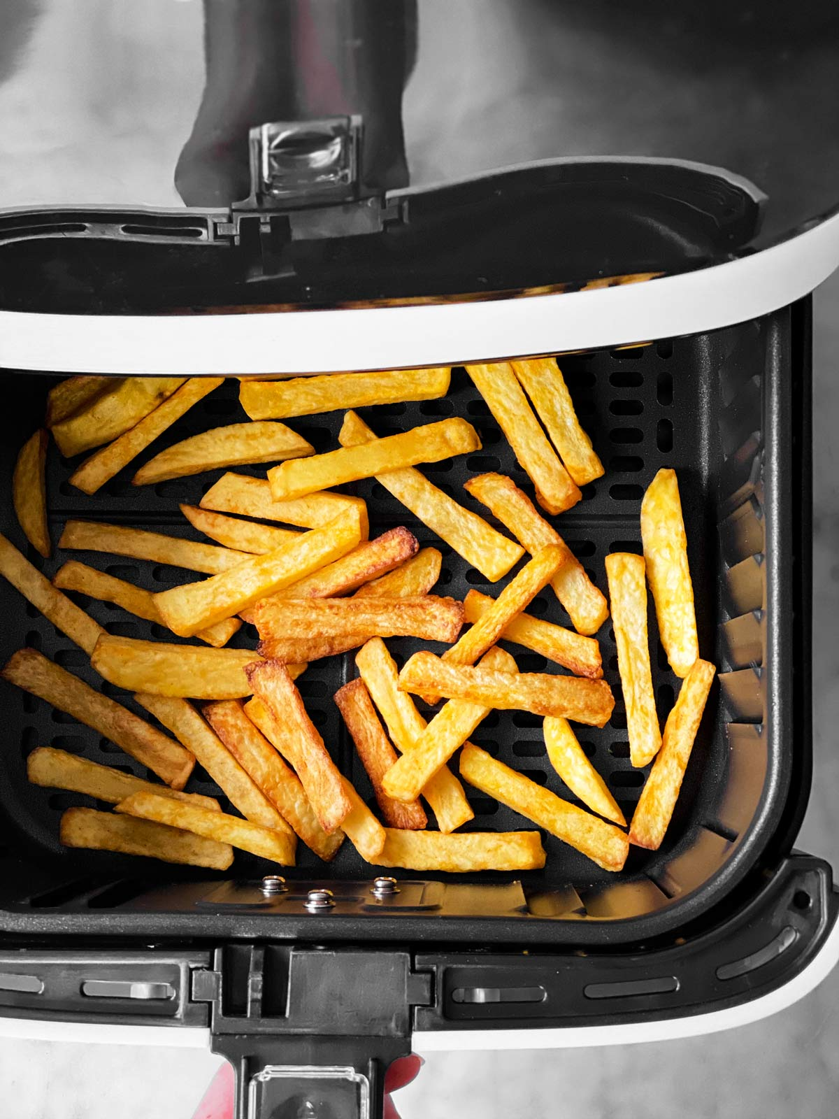 crispy French fries in air fryer basket