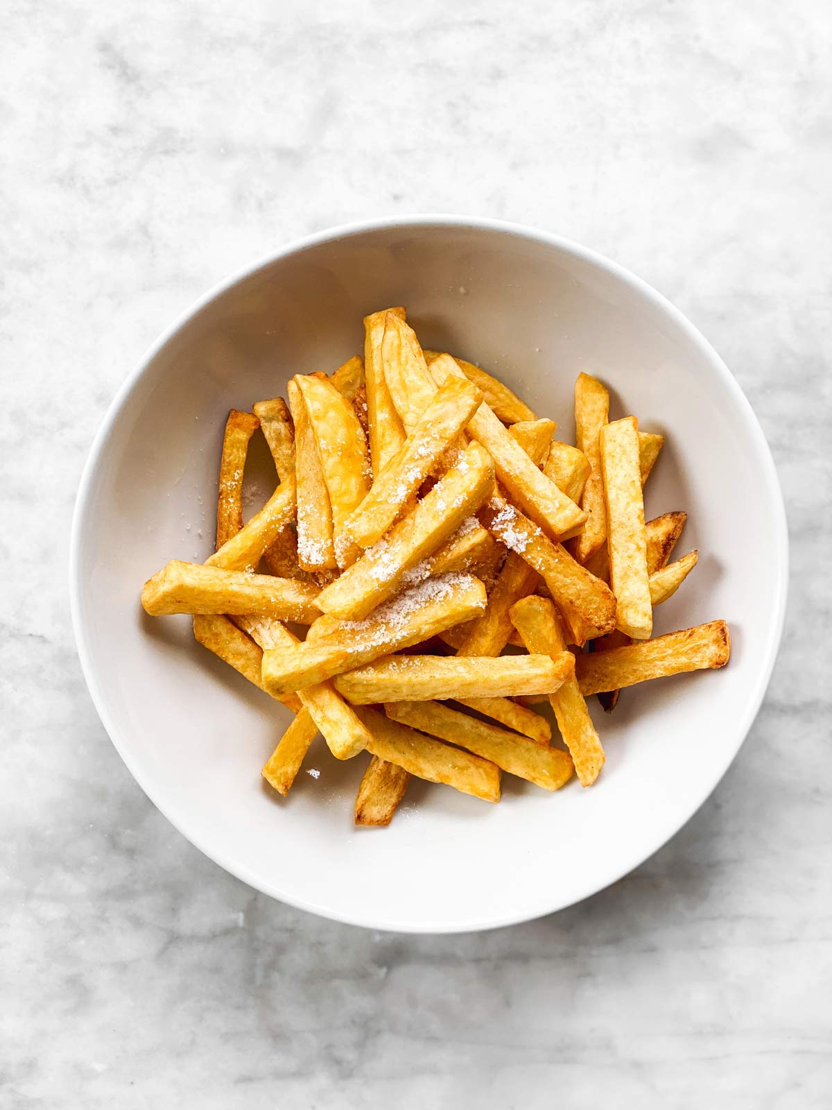 white bowl with French fries and salt