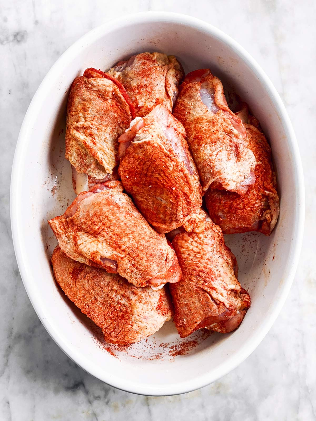 seasoned raw chicken thighs in oval white dish