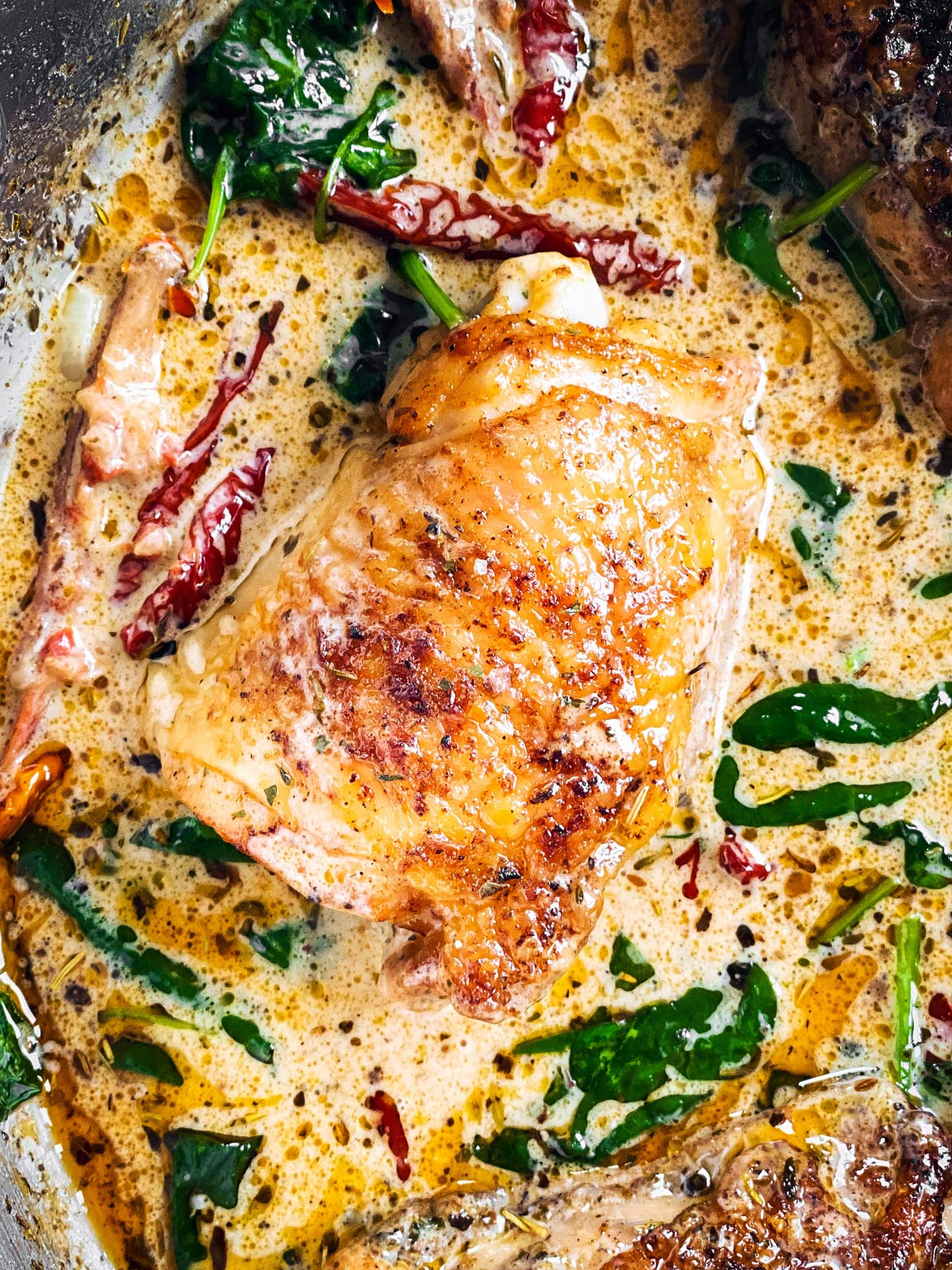 close up photo of chicken thigh in tuscan cream sauce