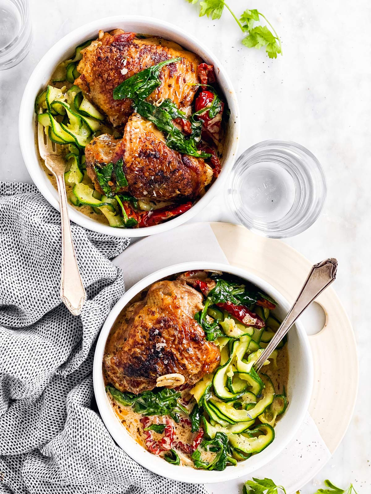 two white bowls with zucchini ribbons and tuscan chicken thighs