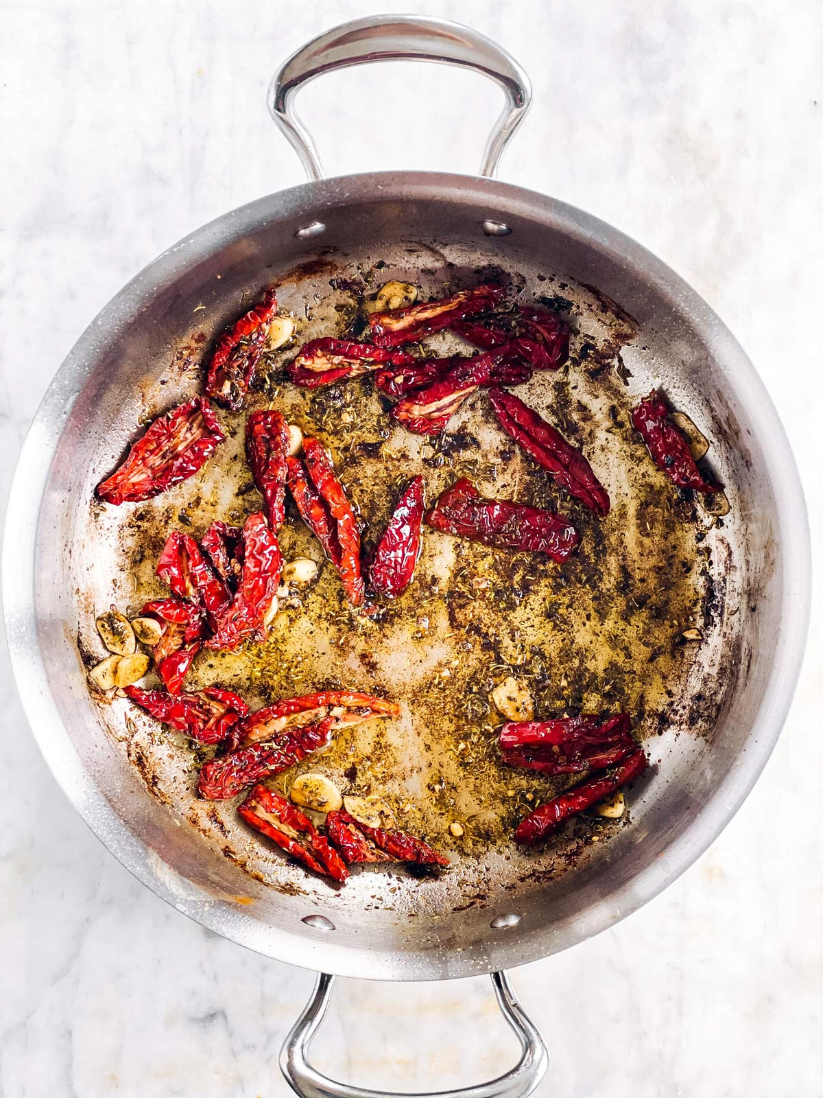skillet with sun-dried tomatoes, oil and seasoning
