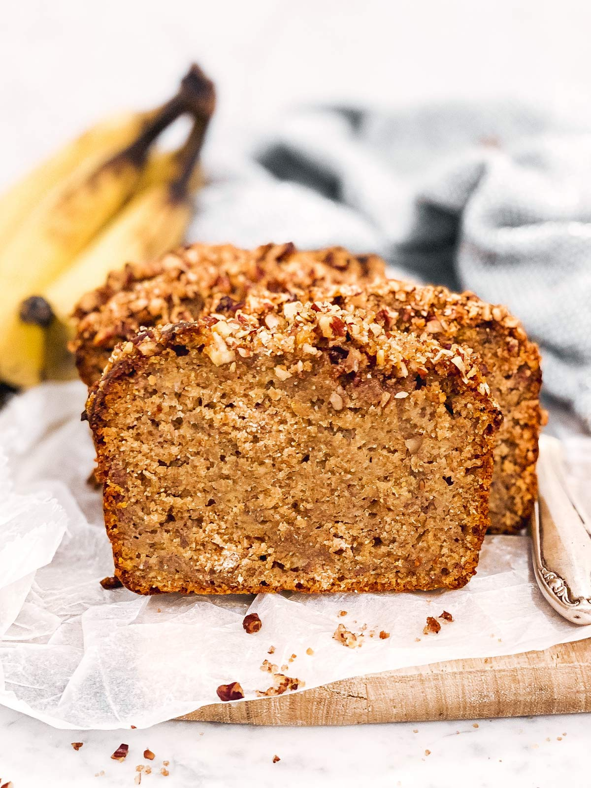 frontal view of sliced banana bread in front of bunch of bananas