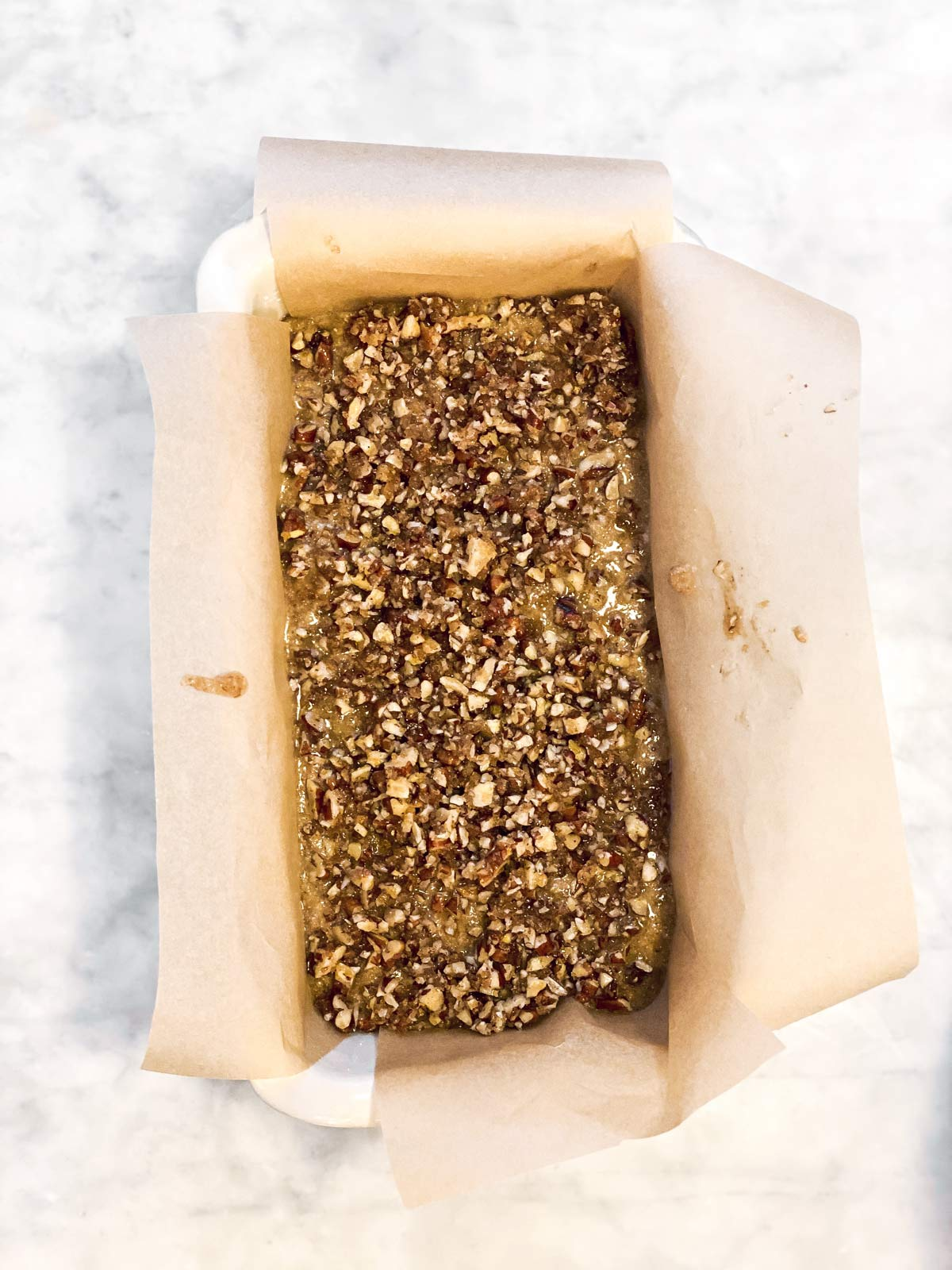 banana bread batter with nut topping in lined loaf pan