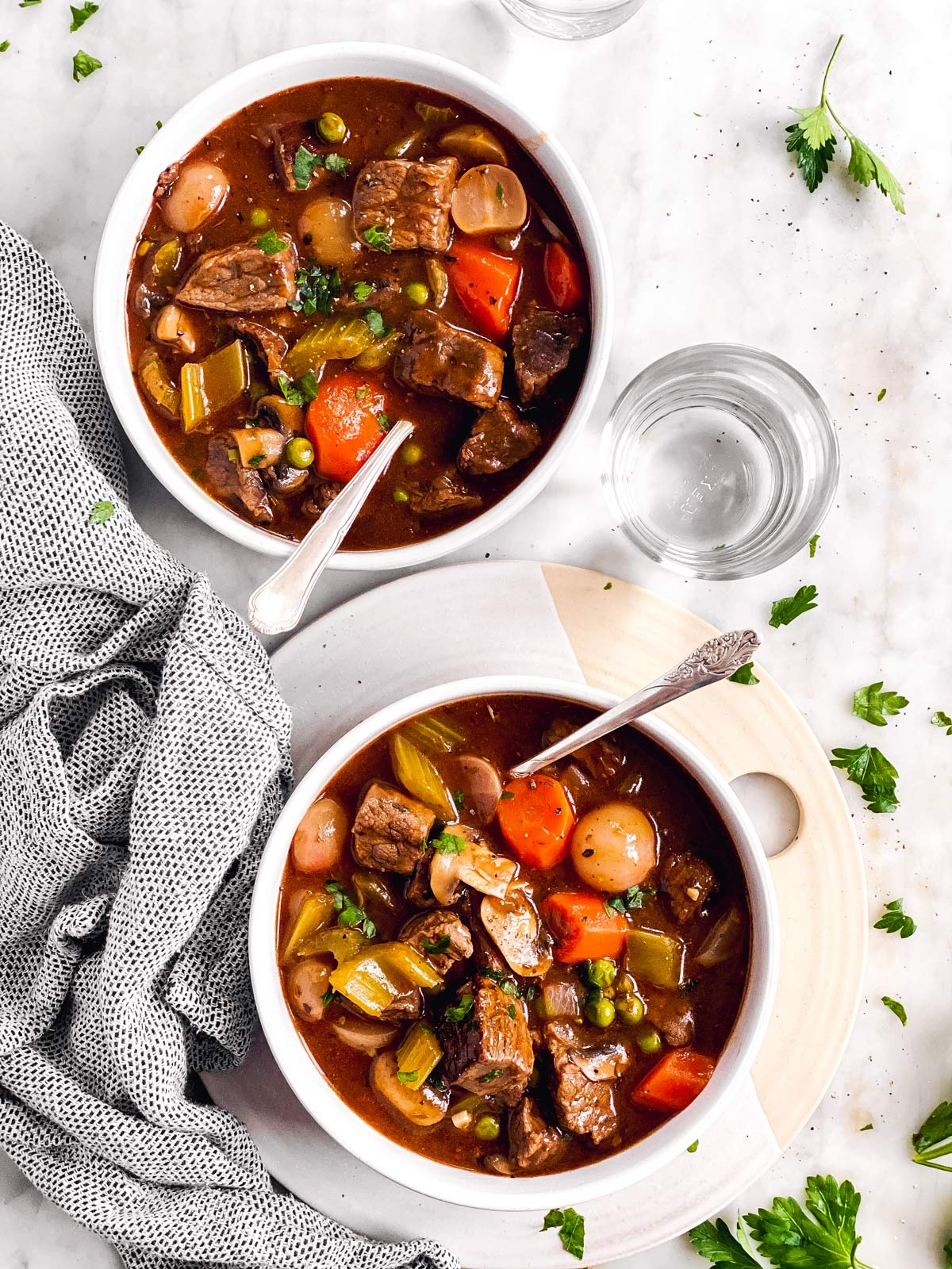 two bowls with keto beef stew on white surface