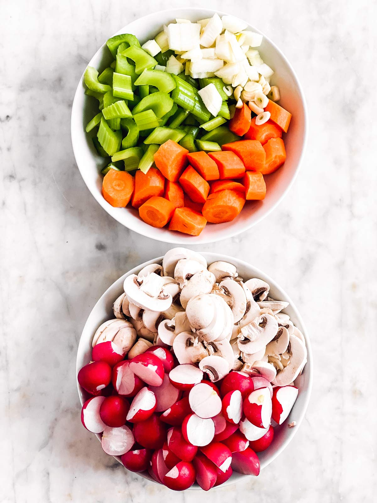 two white bowls with diced stew vegetables