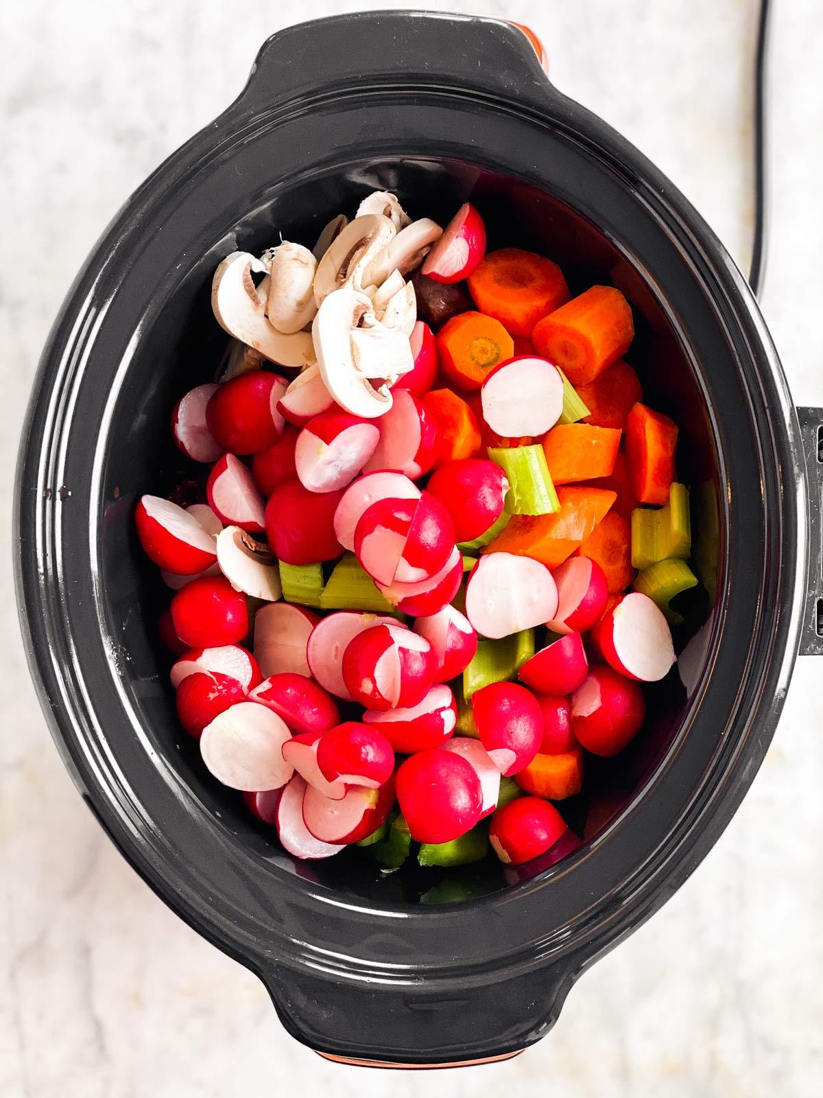 sliced vegetables in black slow cooker