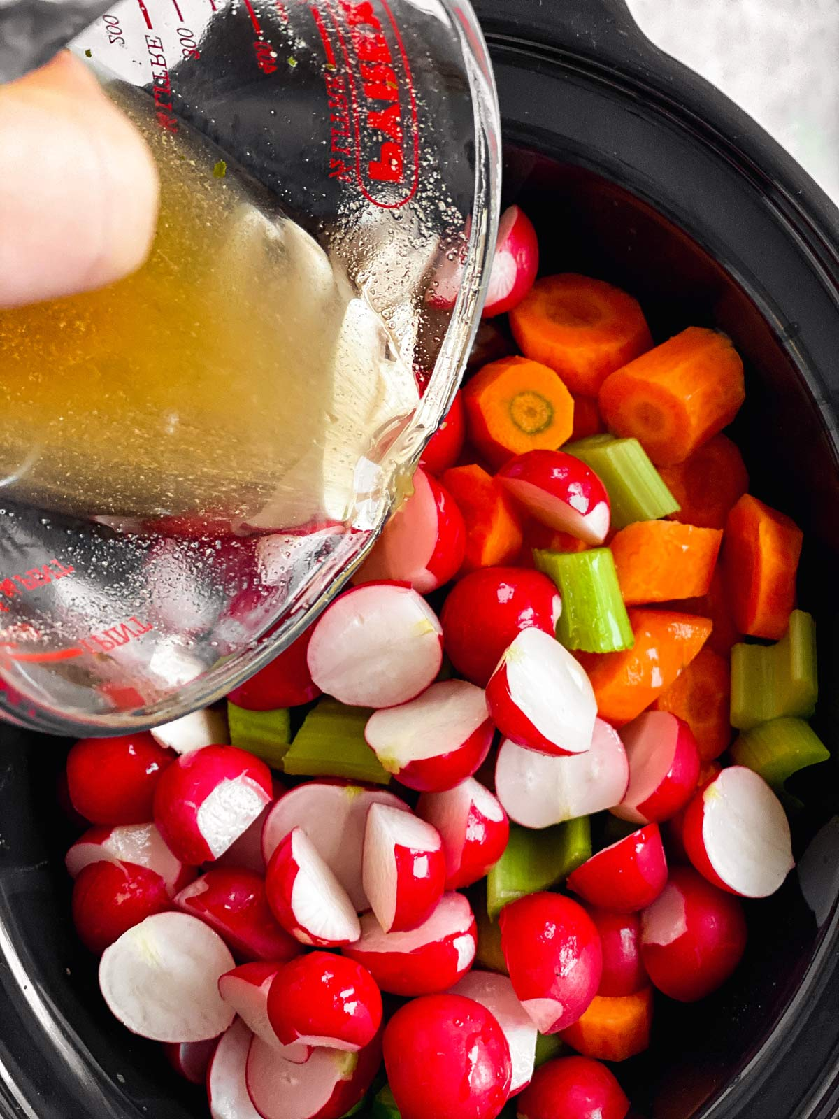 pouring beef broth over sliced vegetables in black slow cooker