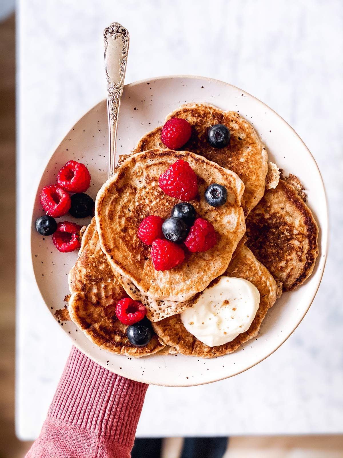 female hand holding white plate with pile of sourdough pancakes and berries