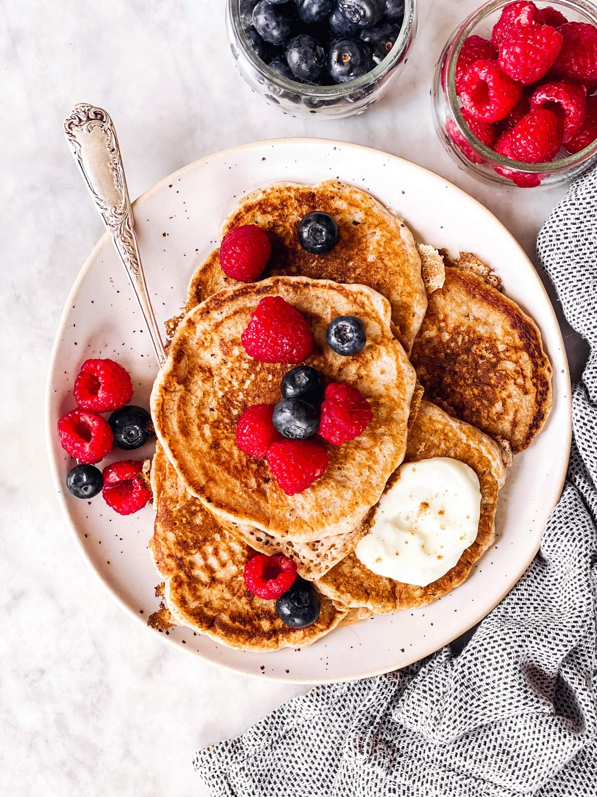 plate with sourdough pancakes and berries on light surface with napkin