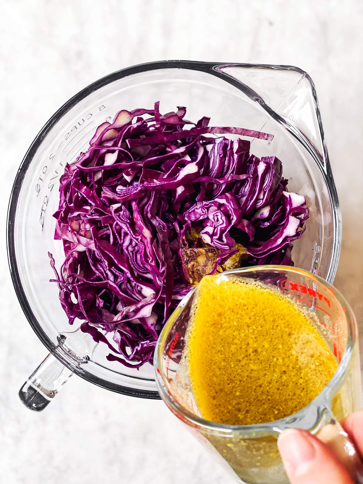 pouring dressing over shredded red cabbage in glass bowl