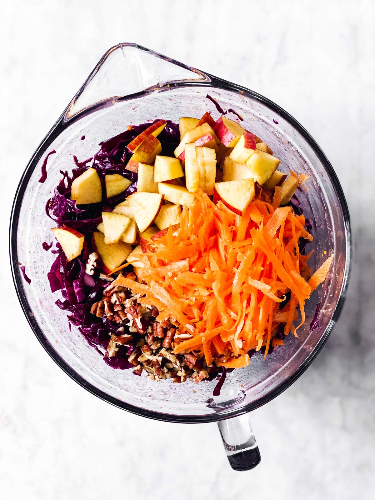 cut apples, chopped pecans and grated carrots on top of shredded red cabbage