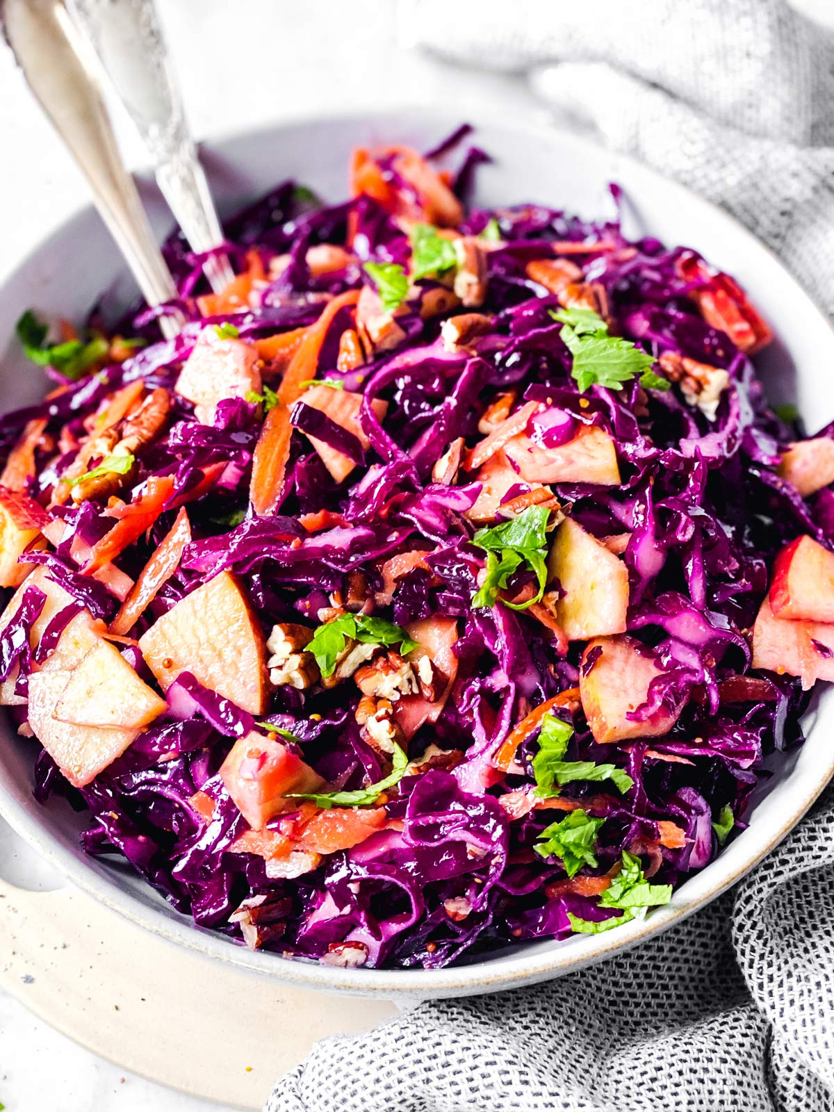 close up salad of red cabbage salad in white bowl