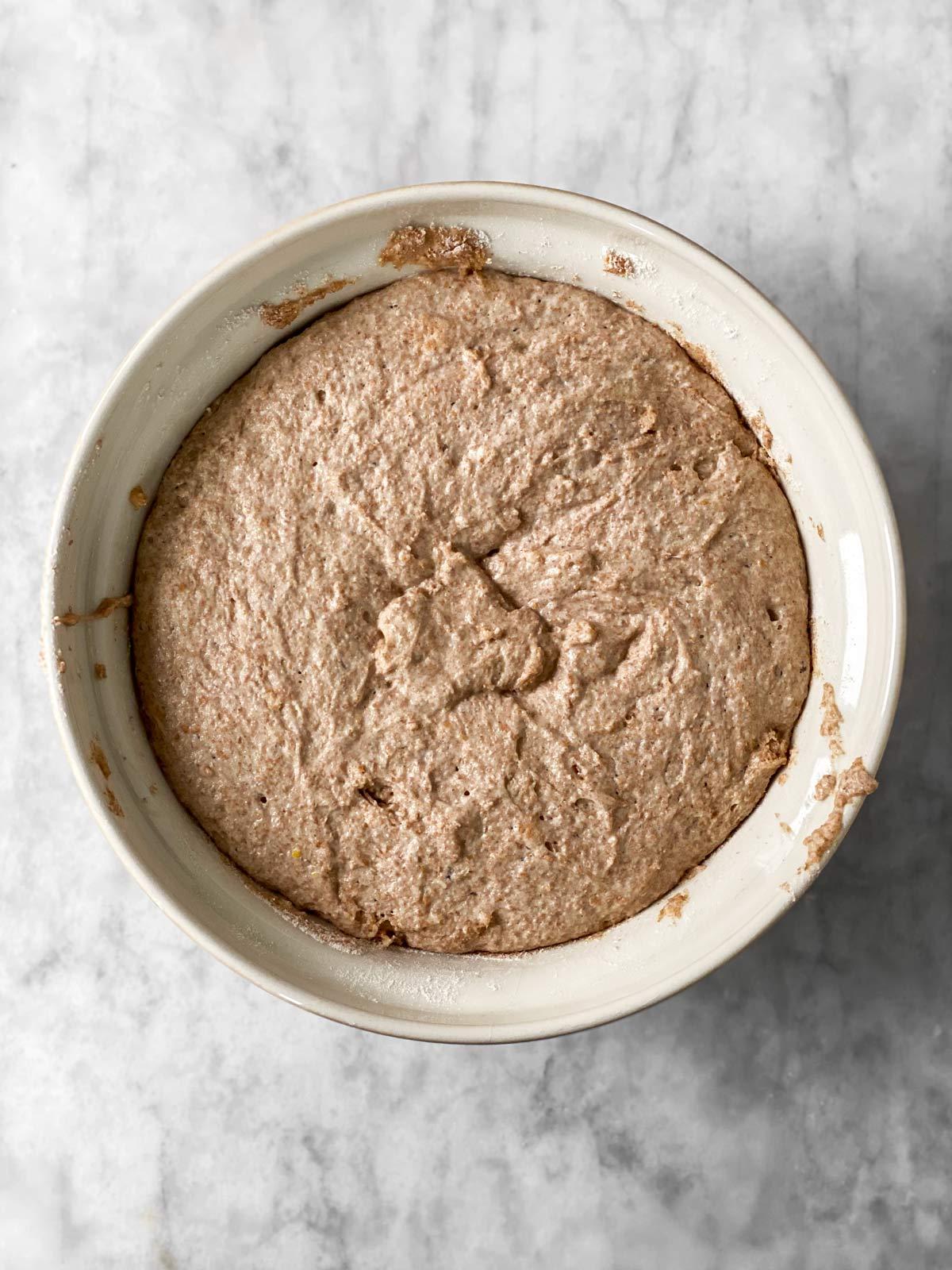 risen whole wheat pizza dough in ceramic bowl